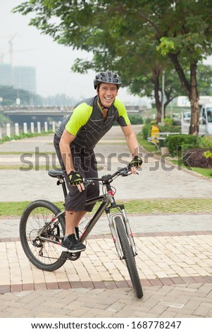 Vertical portrait of a professional biker on his bicycle in the street on the foreground  - stock photo