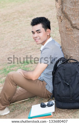 Vertical portrait of a student sitting near the tree outside - stock photo