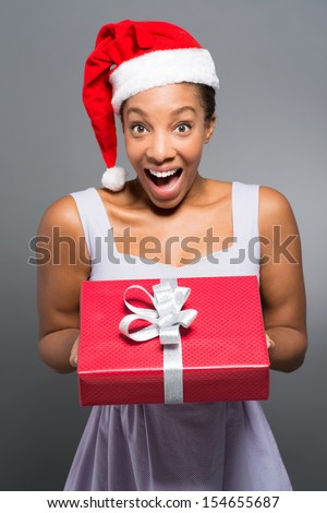 Vertical portrait of a surprised young woman with a x-mas present in hands - stock photo