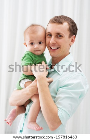 Vertical portrait of a young father holding his little son in hands and looking at camera - stock photo