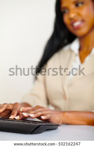Vertical portrait of a young pretty secretary working on computer - stock photo