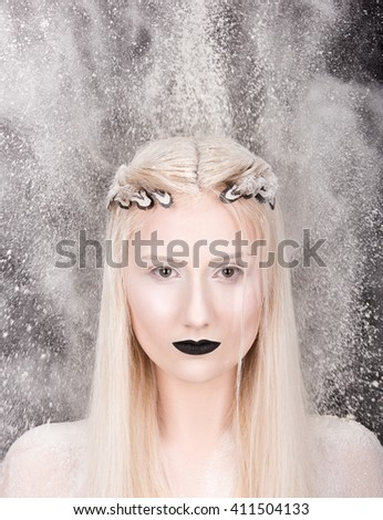 Vertical portrait of a young woman in a white cloud on a black background. Hairstyle with feathers in hair and makeup. Bleached skin and black lipstick - stock photo