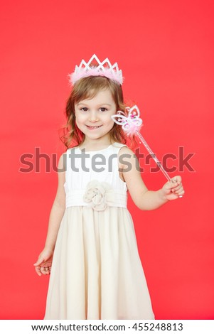 Vertical portrait of beautiful girl dressed in fairy isolated on red background. Cute little kid wearing a crown and white dress holding a magic wand. - stock photo
