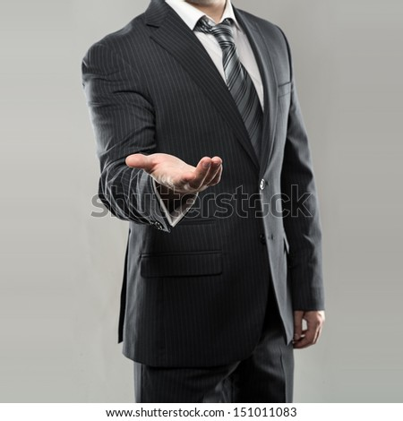 Vertical portrait of businessman or director in luxury suit giving something. Young man with empty hand.  - stock photo
