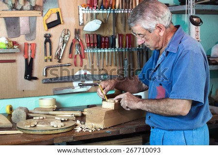 vertical portrait of carpenter marking with pencil handmade pieces of wood workshop / work cabinetmaker marking handcrafted wooden pieces in garage at home   - stock photo