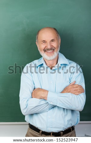 Vertical portrait of Confident expert teacher looking at camera while sitting with arms folded with a blank chalkboard behind - stock photo