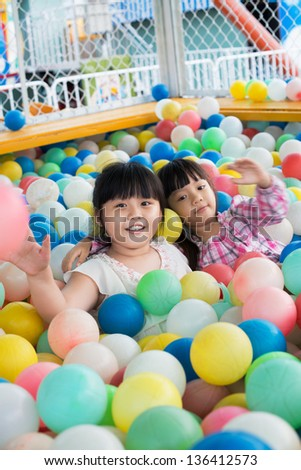 Vertical portrait of playful girls being in a pool full of colorful balls - stock photo