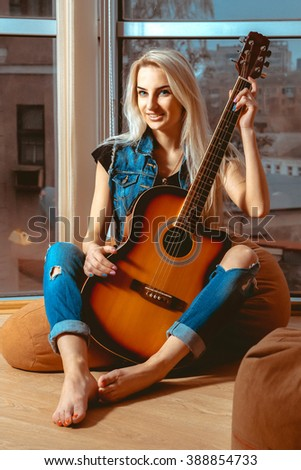 Vertical portrait of pretty cheerful blonde woman with guitar in her hands. Girl with guitar. Woman playing guitar. leisure with guitar. - stock photo