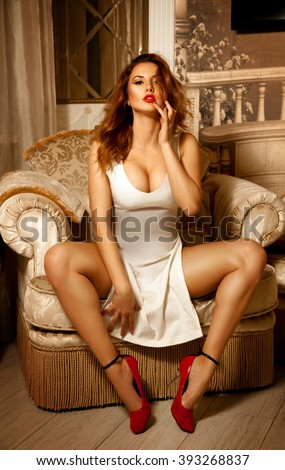 Vertical portrait of sexual lady in white dress posing on chair. Seductive woman. Sexual woman. the concept of seduction, pleasure and desire - stock photo