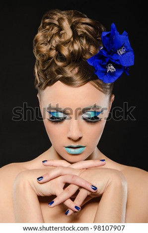Vertical portrait of woman with blue make-up on dark background - stock photo