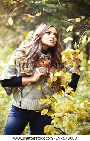Vertical portrait of young blond woman in autumn park - stock photo