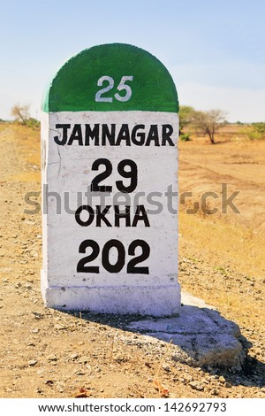 Vertical shot 29 kilometers to Jamnagar direction milestone on main artery infrastructure in Gujarat. Incorporates marker Okha 202 kms, location a barren part of Gujarat on the state highway 25 - SH25 - stock photo