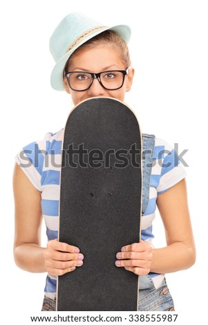 Vertical shot of a blond hipster girl holing a skateboard in front of her face and peeking from behind it isolated on white background - stock photo