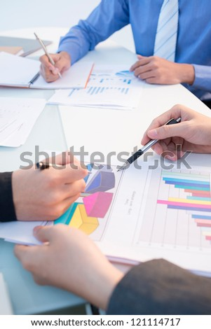 Vertical shot of a business group analyzing statistical data - stock photo
