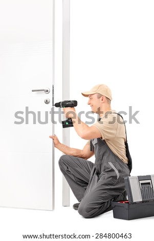 Vertical shot of a cheerful male locksmith installing a door lock with a hand drill isolated on white background - stock photo