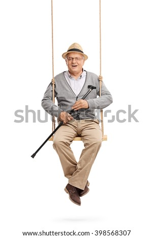 Vertical shot of a cheerful senior holding a cane and sitting on a wooden swing isolated on white background - stock photo