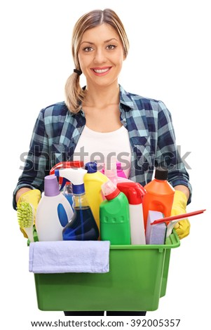 Vertical shot of a cheerful young woman holding a bucket full of cleaning products and equipment isolated on white background - stock photo