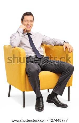 Vertical shot of a confident young businessman sitting in a comfortable yellow armchair isolated on white background - stock photo