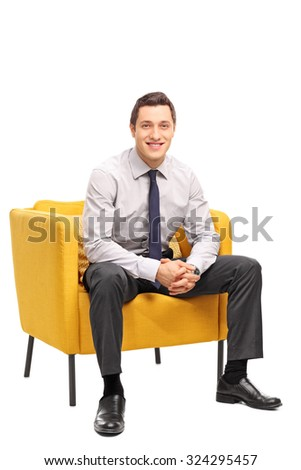 Vertical shot of a confident young businessman sitting in a yellow armchair and looking at the camera isolated on white background - stock photo