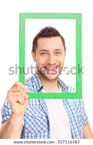 Vertical shot of a confident young man posing behind a green picture frame isolated on white background - stock photo