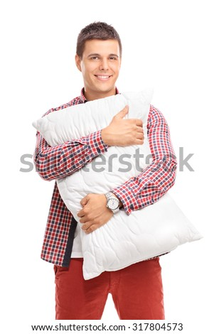 Vertical shot of a content young man hugging a white pillow and looking at the camera isolated on white background - stock photo