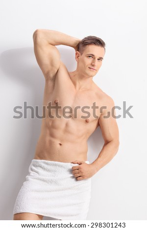 Vertical shot of a handsome young man posing with a white bath towel around his waist and looking at the camera - stock photo
