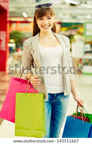 Vertical shot of a happy girl carrying her purchases after shopping - stock photo