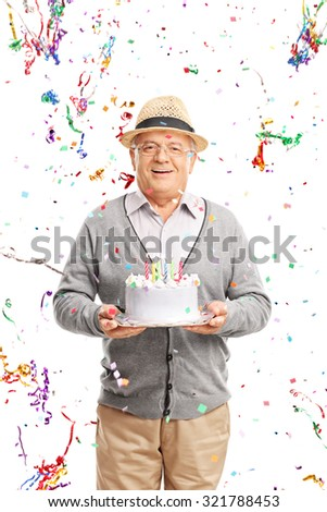 Vertical shot of a joyful senior gentleman carrying a birthday cake with party streamers flying all around him isolated on white background - stock photo