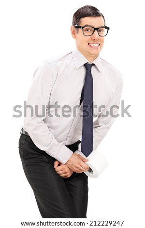 Vertical shot of a man needing to urinate and holding a toilet paper isolated on white background - stock photo