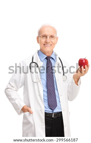 Vertical shot of a mature doctor holding a shiny red apple and looking at the camera isolated on white background - stock photo