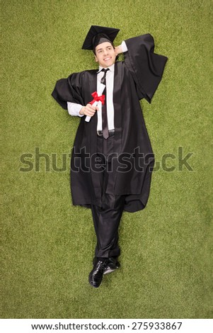 Vertical shot of a pensive young college graduate holding a diploma and lying in a grass field  - stock photo