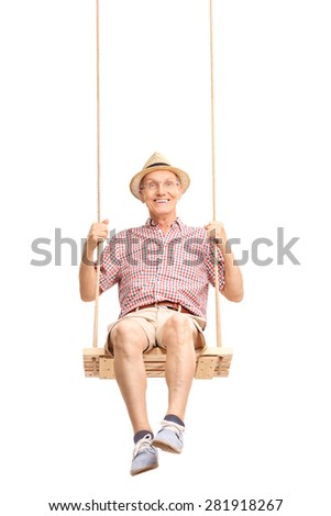 Vertical shot of a playful senior swinging on a swing and looking at the camera isolated on white background - stock photo