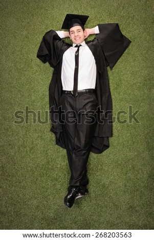 Vertical shot of a relaxed graduate student lying on a grass field and looking at the camera - stock photo