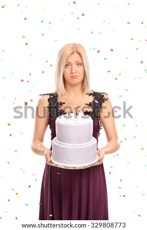 Vertical shot of a sad young woman holding a birthday cake with confetti streamers flying around her isolated on white background - stock photo