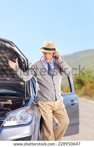 Vertical shot of a senior having a problem with his car on an open road - stock photo