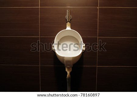 Vertical shot of a toilet on a brown background - stock photo