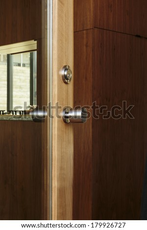 Vertical shot of a wood framed door with glass and view of modern handle/Luxury door with chrome door knob and glass window - stock photo