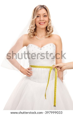Vertical shot of a young bride posing in a wedding dress and someone measuring her waist isolated on white background - stock photo