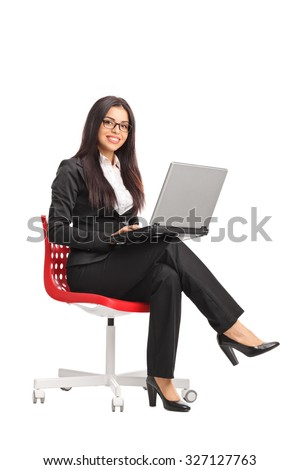Vertical shot of a young businesswoman holding a laptop and looking at the camera seated on a red chair isolated on white background - stock photo