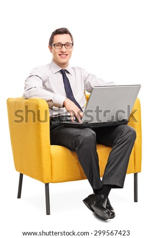 Vertical shot of a young cheerful businessman working on a laptop seated in a yellow armchair isolated on white background - stock photo