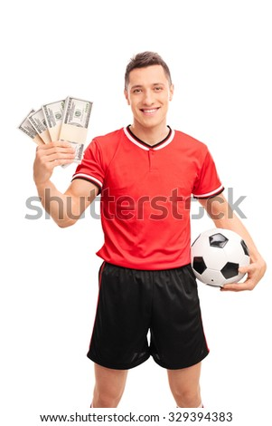 Vertical shot of a young male football player holding a few stacks of money and smiling isolated on white background - stock photo