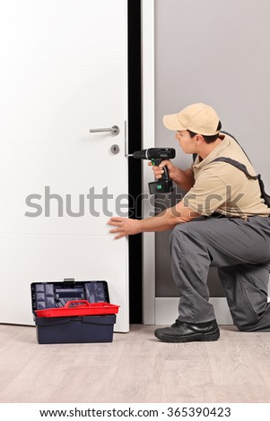 Vertical shot of a young male locksmith installing a door lock with an electric hand drill  - stock photo