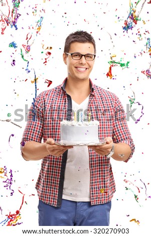 Vertical shot of a young man carrying a birthday cake with confetti all around him isolated on white background - stock photo