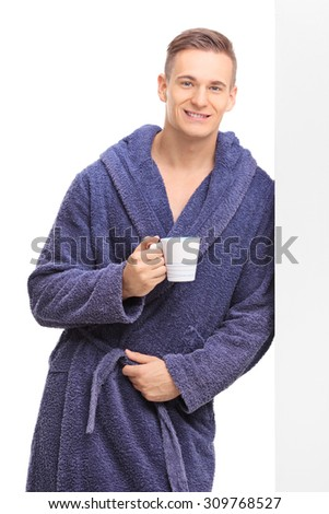 Vertical shot of a young man in a blue bathrobe holding a cup of coffee and leaning against a wall isolated on white background - stock photo