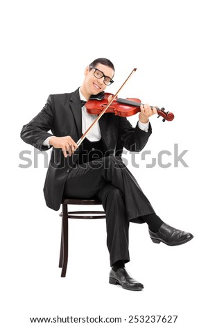 Vertical shot of a young violinist playing a violin seated on a chair isolated on white background - stock photo