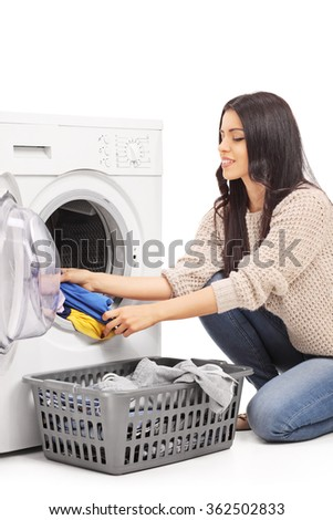 Vertical shot of a young woman emptying a washing machine isolated on white background - stock photo