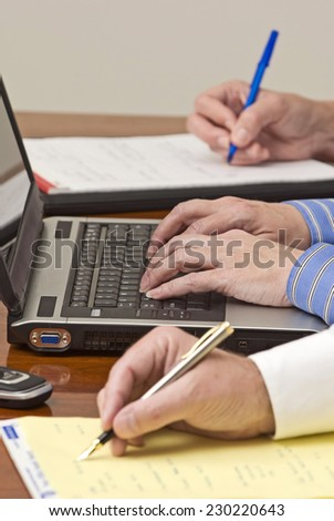 Vertical Shot Of Business People Taking Notes At Business Meeting/ Focus On Center Not Front Of Picture - stock photo
