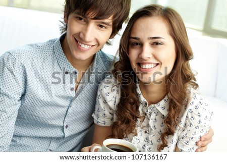 Vertical shot of happy sweethearts posing in front of camera - stock photo