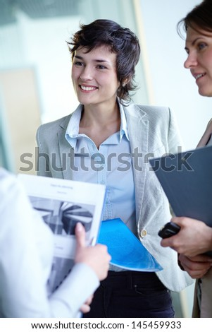 Vertical shot of lovely businesswomen communicating in a group - stock photo