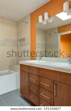 Vertical shot of modern bathroom featuring double sink fixtures and bathtub - stock photo